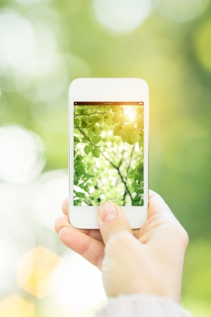 Woman holding smartphone against spring green background  Ecology concept photo
