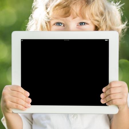 Dzieci: Happy dziecko gospodarstwa zewnÄ…trz Tablet PC w parku wiosnÄ…
