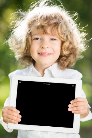 Happy smiling child holding tablet PC against green spring background Stock Photo - 17642605