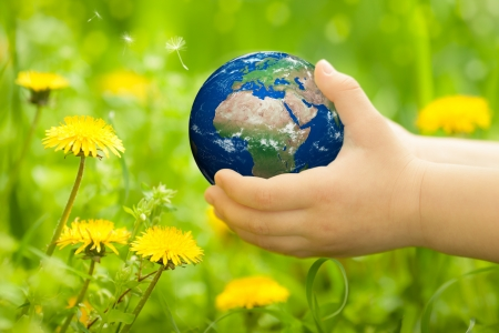 Planet Earth in children s hands against spring flowers  Elements of this image furnished by NASA photo
