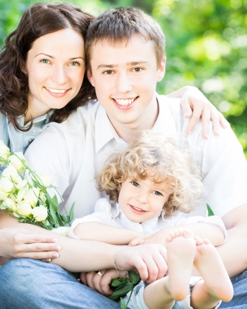 Happy family with bouquet of spring flowers against blurred green background photo