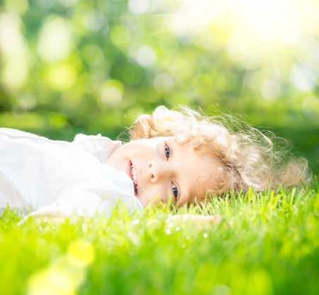 Happy child lying on green grass against spring sunny background photo