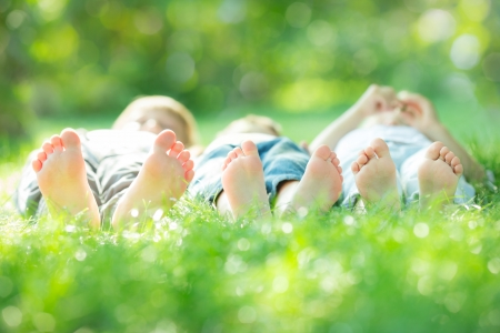 relaxation exercise: Happy active family lying on green grass in spring park
