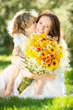 Happy child giving big bouquet of spring flowers to woman for mother`s day  photo