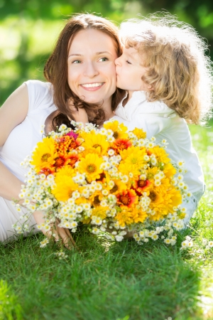 Child with big bouquet of spring flowers kissing happy smiling woman. Mother`s day concept Stock Photo