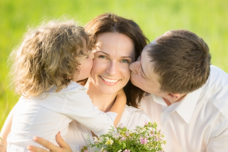 Happy family having fun outdoors in spring green field photo