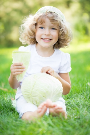 Happy smiling child with vegetables sitting on grass outdoors in spring park against green blurred background. Healthy eating concept photo