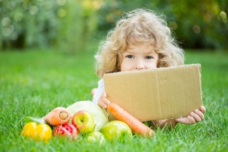 Happy child with fruits and vegetables lying on grass outdoors in spring park against green blurred background. Healthy eating concept. Paper blank with copyspace photo