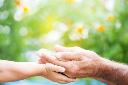 Senior man and baby holding empty hands against green spring background Stock Photo - 18086173