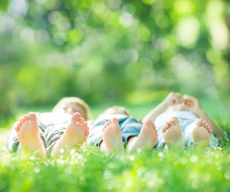happy kids: Happy family lying on green grass in spring park. Healthy lifestyle concept. Farmland vacations Stock Photo