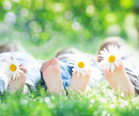 pies bonitos: Los pies sanos de la familia con flores de la margarita en hierba verde contra el fondo borroso primavera. Farmland concepto vacaciones Foto de archivo