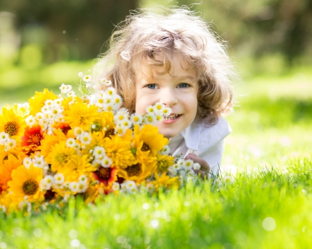 Happy child with big bouquet of spring flowers lying on green grass. Mothers day celebration concept photo