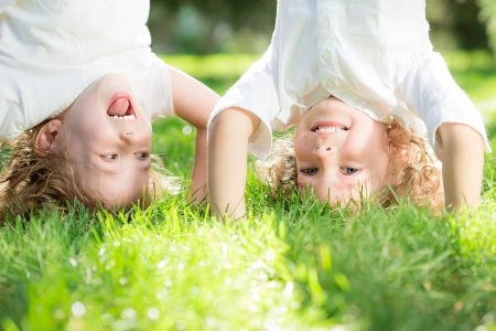 headstand: Happy children standing upside down on green grass in spring park. Healthy lifestyles concept.