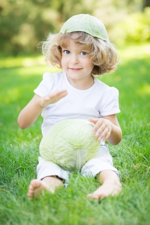 Happy child playing with vegetables on green grass in spring park  Healthy eating concept photo