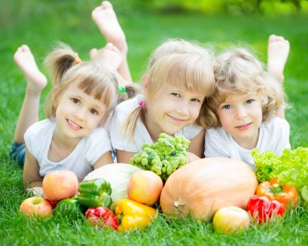 Grupo de crianças felizes com frutas e legumes deitado na grama verde ao ar livre no parque da mola Banco de Imagens - 18347193
