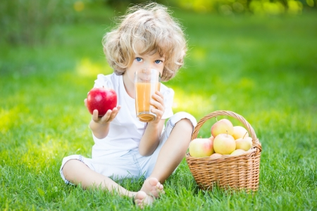 Happy child sitting on green grass and drinking apple juice in spring park photo