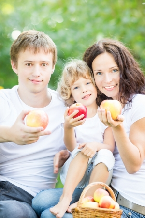 Happy family eating fruits outdoors in spring park against green background  Healthy lifestyle concept photo