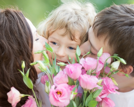 Happy family with bouquet of spring flowers  Mother and father kissing your child against natural green background  Celebration concept photo