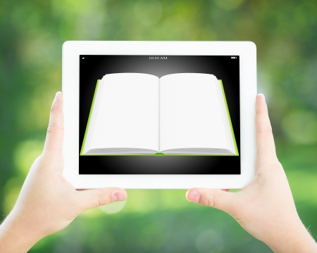 Student holding tablet PC with ebook in hands against spring green background  Education technology concept photo