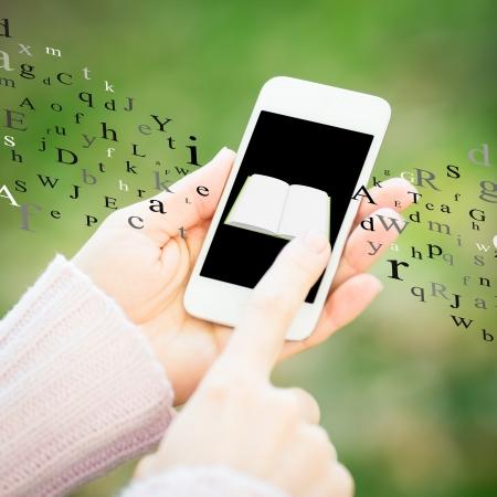 Smartphone avec le livre dans les mains agaist femme fond vert printemps Banque d'images