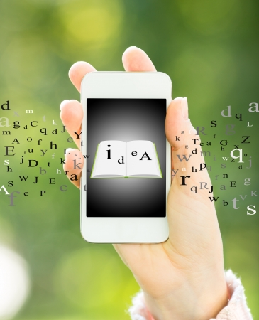 Woman holding smart phone with ebook in hand against green spring background Stock Photo - 18153487