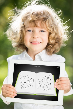 Happy smiling child holding tablet PC with ebook against green spring background  Education technology concept photo