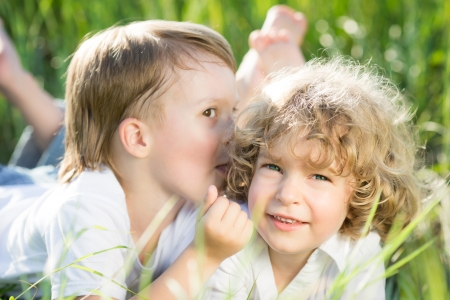 Happy children playing outdoors in spring grass Stock Photo - 18153545