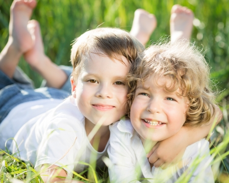 boy barefoot: Happy smiling children playing outdoors in spring grass