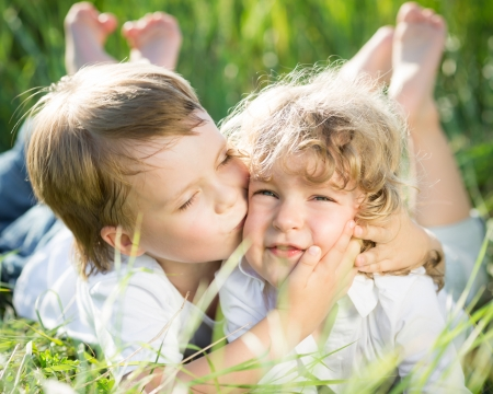 secret love: Happy children playing outdoors in spring grass
