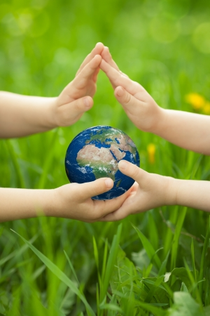 Planet Earth in children s hands against green spring background photo
