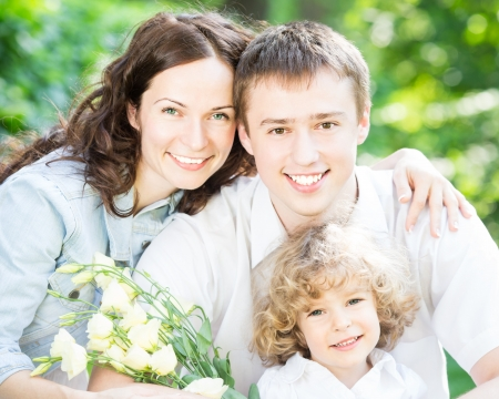 Happy family with bouquet of flowers having fun outdoors in spring park against natural green background. Mothers day celebration concept photo