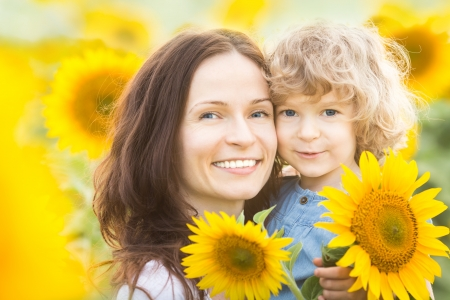 Happy family with sunflowers having fun outdoors in spring field photo