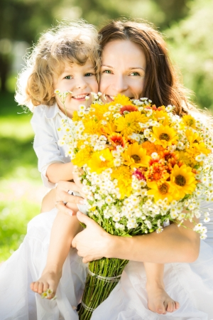 Happy family with big bouquet of spring flowers having fun outdoors against blurred green background. Mothers day celebration concept photo