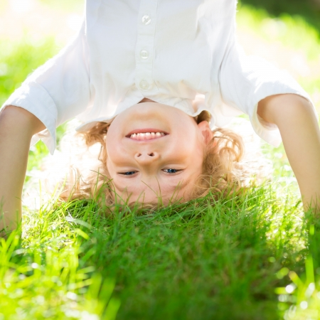 headstand: Happy smiling kid playing on green grass in spring park. Healthy lifestyle concept. Children`s fitness Stock Photo