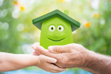 hand holding house: Family holding eco cartoon house in hands against green spring background. Environment protection concept Stock Photo