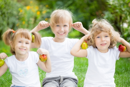 Happy active kids with apples having fun in spring park  Healthy eating concept photo