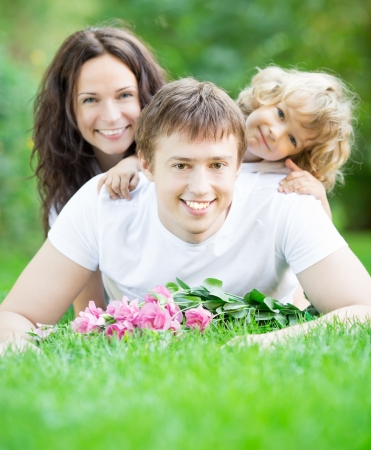 Happy family lying on grass in spring park against blurred green background Stock Photo - 18347117