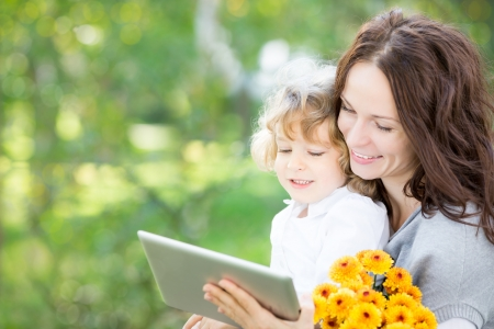 tablet pc in hand: Happy family with bouquet of spring flowers using tablet PC outdoors Stock Photo