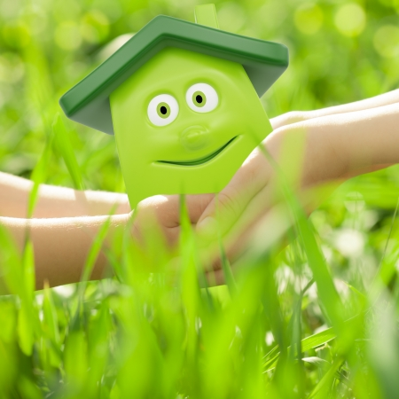 eco building: Eco cartoon house in hands against spring green background  Family home concept