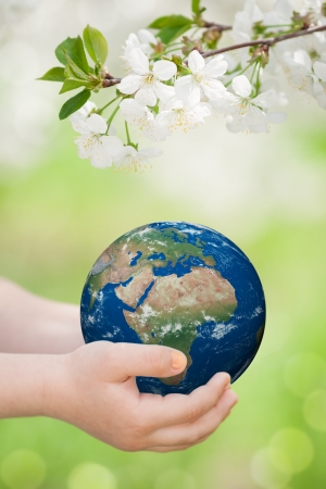 earth day: Child holding world in hands against green spring background  Earth day concept  Elements of this image furnished by NASA