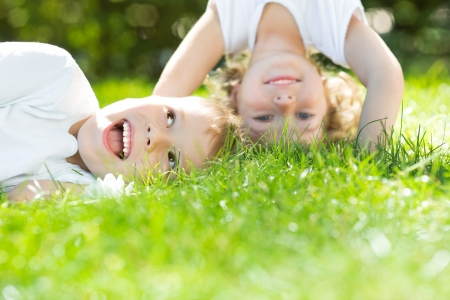 headstand: Happy children standing upside down on green grass in spring park  Healthy lifestyles concept