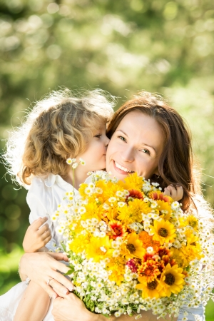 Family with big bouquet of spring flowers  Child kissing woman  Mothers day concept photo