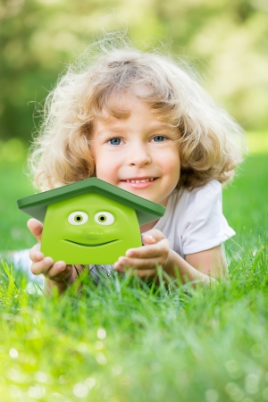 Happy child holding 3d house in hands and lying on green grass in spring park  Ecology concept photo