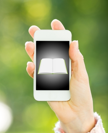 Smartphone with book in woman hand against green spring background photo