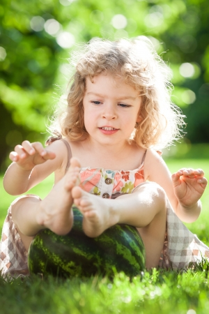 Happy child playing with big watermelon on green grass in summer park  Healthy eating concept photo