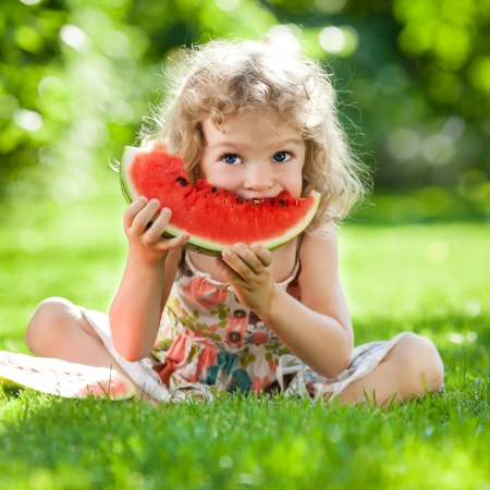 Happy child with big red slice of watermelon sitting on green grass in summer park  Healthy eating concept Stockfoto