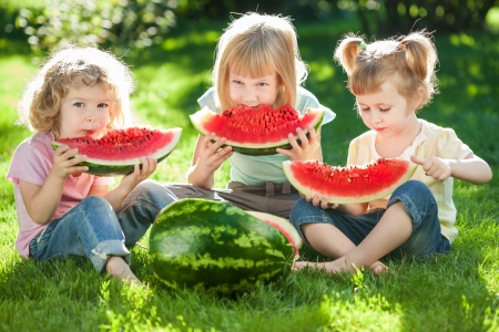 eating in: Group of happy kids eating watermelon on green grass in summer park