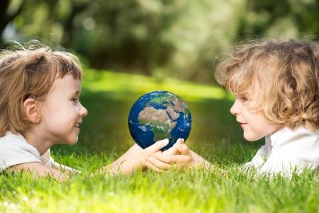 Kinder s hält Welt in den Händen gegen den grünen Frühling Hintergrund Tag der Erde-Konzept Standard-Bild