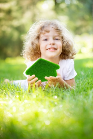 eco building: Child holding green grass house in hands  Ecology concept