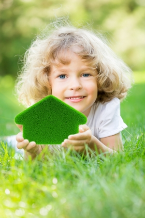 eco house: Happy child holding green grass house in hands  Ecology concept
